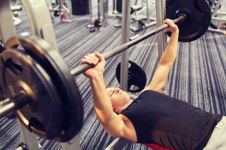 sport, bodybuilding, lifestyle and people concept - young man with barbell flexing muscles and making bench press in gym