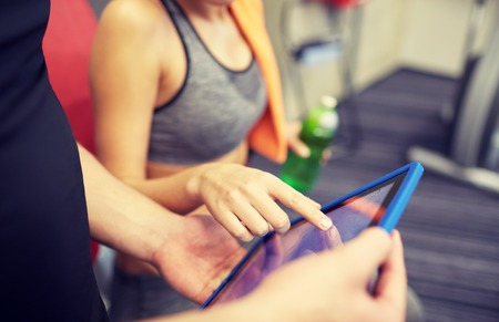 sport, fitness, lifestyle, technology and people concept - close up of trainer hands with tablet pc computer and woman working out in gym Stock Photo