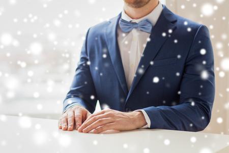 Menschen, Mode, Stil und Hochzeit Konzept - in der Nähe der besten Mann oder Bräutigam in Anzug und Krawatte am Tisch mit fallendem Schnee-Effekt
