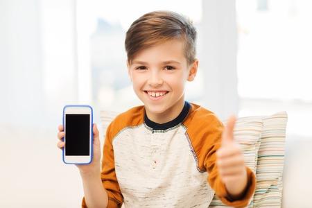 personas felices: el ocio, los ni�os, la tecnolog�a, la publicidad y la gente concepto - muchacho sonriente con el tel�fono inteligente en el hogar Foto de archivo
