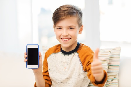 happy people: leisure, children, technology, advertisement and people concept - smiling boy with smartphone at home