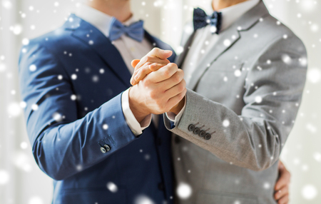 sex: mensen, homoseksualiteit, het homohuwelijk en de liefde concept - close-up van gelukkige mannen homoseksueel stel hand in hand en dansen op de bruiloft over sneeuw effect