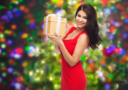 sexy dress: people, holidays, christmas, birthday and celebration concept - beautiful sexy woman in red dress with gift box over party lights background