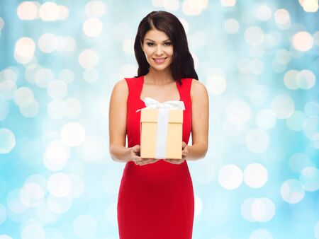 sexy birthday: people, holidays, christmas, birthday and celebration concept - beautiful sexy woman in red dress with gift box over blue lights background