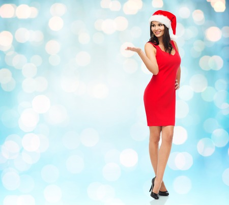 something: people, holidays, christmas and advertisement concept - beautiful sexy woman in santa hat and red dress showing something on empty hand over blue lights background Stock Photo