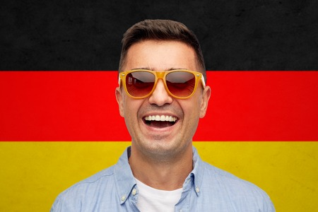 citizenship: summer, accessories, patriotism, citizenship and people concept - face of smiling middle aged latin man in shirt and sunglasses over german flag background