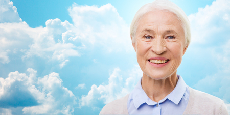 mature female: age and people concept - happy smiling senior woman face over blue sky and clouds background Stock Photo