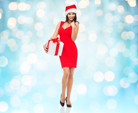 red and blue: people, holidays, christmas and celebration concept - beautiful sexy woman in red dress and santa hat with gift box over blue lights background Stock Photo