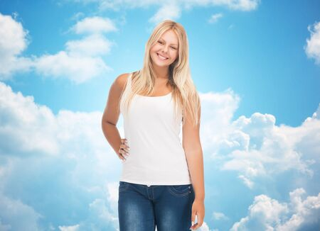 overweight students: people, holidays, style and body type concept - smiling young woman in blank white shirt and jeans over blue sky and clouds background
