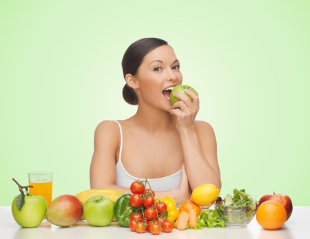 over weight: people, food, diet and weight loss concept - happy woman with fruits and vegetables eating apple over green background