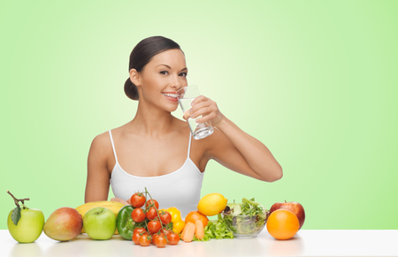 woman diet: people, food, diet, healthy eating and weight loss concept - happy beautiful woman with fruits and vegetables drinking water over green background
