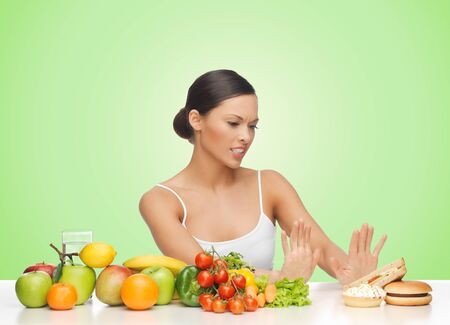 rejecting: people, junk food, healthy eating, diet and weight loss concept - woman with fruits and vegetables rejecting hamburger over green background
