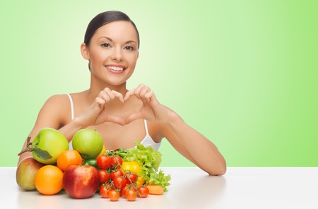 people, food, diet, healthy eating and weight loss concept - happy beautiful woman with fruits and vegetables showing heart shape hand sign over green background