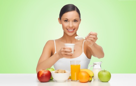 over eating: people, healthy food, diet and weight loss concept - happy beautiful woman with fruits eating yogurt for breakfast over green background Stock Photo