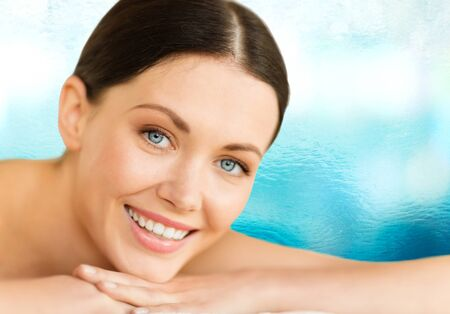 health and beauty, resort and relaxation concept - woman in spa salon lying on the massage desk Stock Photo