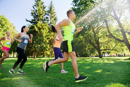 sportsmen: fitness, sport, friendship, race and healthy lifestyle concept - group of happy teenage friends or sportsmen running marathon with badge numbers outdoors