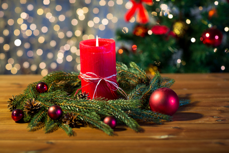 christmas candle: christmas, decoration, holidays and advertisement concept - close up of natural green fir branch wreath with red burning candle on wooden board Stock Photo