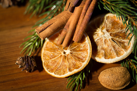 decoration objects: decoration, winter, holidays and new year concept - close up of christmas fir branch with cinnamon and dried orange on wooden table Stock Photo