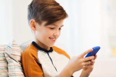 vrije tijd, kinderen, technologie, internet communicatie en mensen concept - lachende jongen met smartphone sms-bericht of playing game thuis