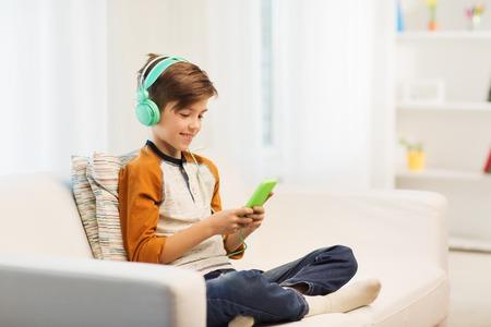 personas escuchando: ocio, los ni�os, la tecnolog�a y el concepto de la gente - muchacho con el tel�fono inteligente y los auriculares escuchando m�sica o jugando juegos en su casa sonriendo
