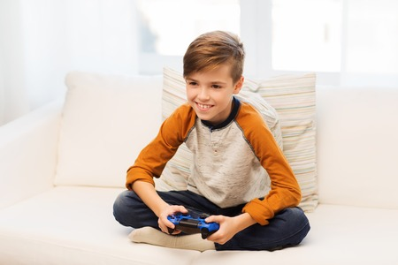 kids playing video games: leisure, children, technology and people concept - smiling boy with joystick playing video game at home