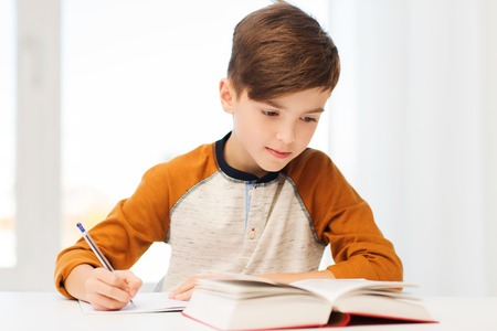 education, childhood, people, homework and school concept - student boy with book writing to notebook at home