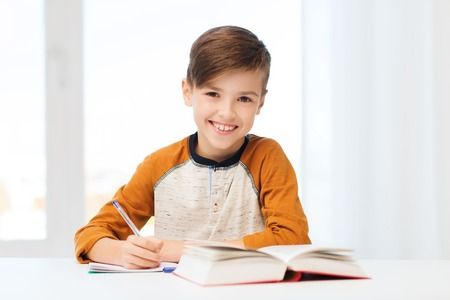 school boy: education, childhood, people, homework and school concept - smiling student boy with book writing to notebook at home Stock Photo
