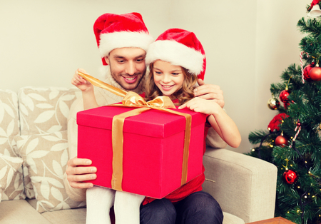 huge christmas tree: family, christmas, x-mas, winter, happiness and people concept - smiling father and daughter in santa helper hats opening gift box