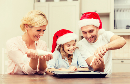 hapiness: food, family, christmas, hapiness and people concept - smiling family in santa helper hats decorating cookies with glaze Stock Photo