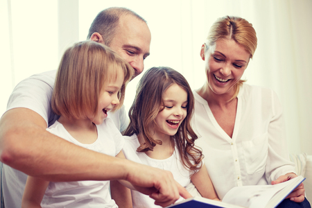 preteen: family, childhood, holidays and people - smiling mother, father and little girls reading book at home Stock Photo
