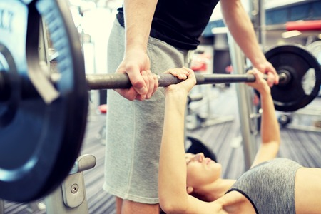 personal safety: sport, fitness, teamwork, weightlifting and people concept - close up of young woman and personal trainer with barbell flexing muscles in gym