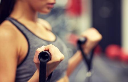 фитнес: спорт, фитнес, образ жизни и люди концепции - крупным планом молодой женщины сгибание мышцы на кабель тренажерном зале машины