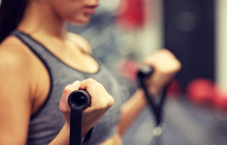 gym: sport, fitness, lifestyle and people concept - close up of young woman flexing muscles on cable gym machine Stock Photo
