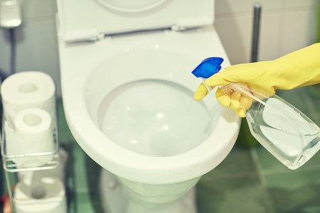 toilet: people, housework and housekeeping concept - close up of hand in rubber glove with detergent cleaning toilet pan