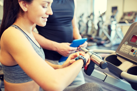 heartrate: sport, fitness, lifestyle, technology and people concept - close up of woman setting heart-rate watch at gym with trainer