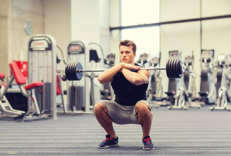 male chest: sport, bodybuilding, lifestyle and people concept - young man with barbell doing squats in gym