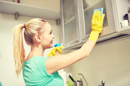 orden y limpieza: las personas, el trabajo doméstico y el concepto de servicio de limpieza - feliz gabinete limpieza de la mujer con un trapo y un limpiador en la cocina en casa