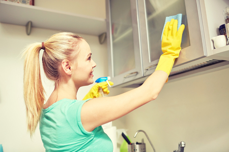 housewife gloves: people, housework and housekeeping concept - happy woman cleaning cabinet with rag and cleanser at home kitchen