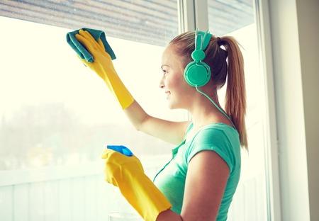 orden y limpieza: las personas, el trabajo doméstico y el concepto de servicio de limpieza - mujer feliz en los auriculares escuchando música y la ventana de limpieza con un limpiador en casa
