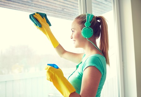chores: people, housework and housekeeping concept - happy woman in headphones listening to music and cleaning window with cleanser at home