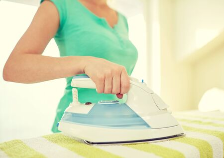 orden y limpieza: people, housework, laundry and housekeeping concept - close up of happy woman with iron and ironing board at home