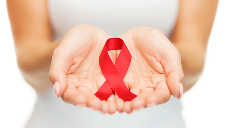 hiv ribbon: healthcare and medicine concept - female hands holding red AIDS awareness ribbon Stock Photo