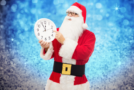 12 month old: christmas, holidays, time and people concept - man in costume of santa claus with clock showing twelve pointing finger over blue glitter or lights background Stock Photo