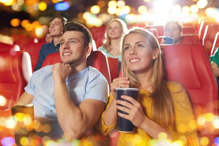 at leisure: cinema, entertainment and people concept - happy friends watching movie in theater