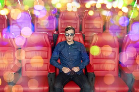 empty of people: cinema, technology, entertainment and people concept - young man with 3d glasses watching movie alone in empty theater auditorium