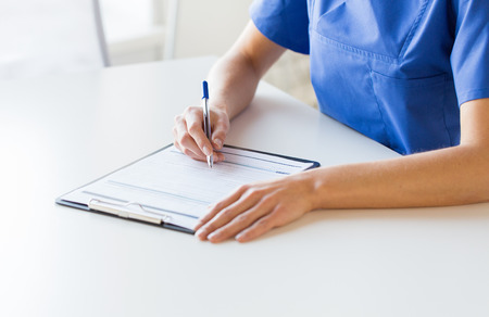 pielęgniarki: medycyna, ludzie i koncepcja opieki zdrowotnej - Zamknij się kobieta lekarza lub pielęgniarki pisanie raportu medycznego do schowka w szpitalu