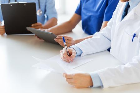 profesiones: la educación, la profesión, la gente y concepto de la medicina - Cierre de médicos felices con la tablilla del ordenador PC y papeles en el seminario o en el hospital