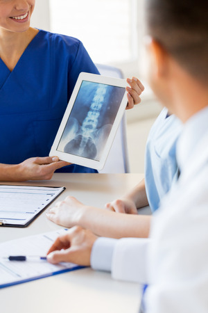 a medical technology: technology, surgery, people and medicine concept - close up of happy doctors discussing x-ray on tablet pc computer at hospital,