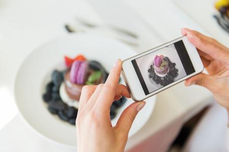 사람들, 휴일, 기술, 음식과 생활 양식 개념 - 가까운 스마트 폰이 레스토랑에서 디저트의 사진을 복용하는 여성의 최대