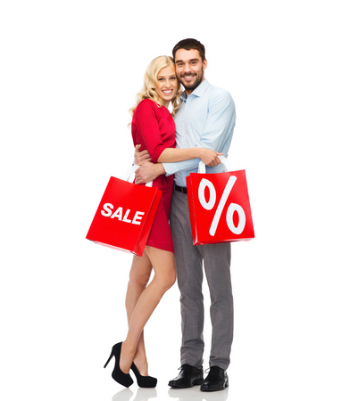 happy family shopping: people, sale, discount and holidays concept - happy couple hugging with red shopping bags